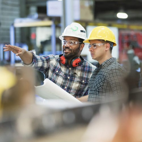 Multi-ethnic workers talking in metal fabrication plant