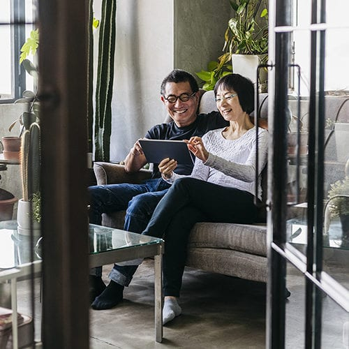Cheerful Chinese Woman Showing Man Digital Tablet In Conservatory
